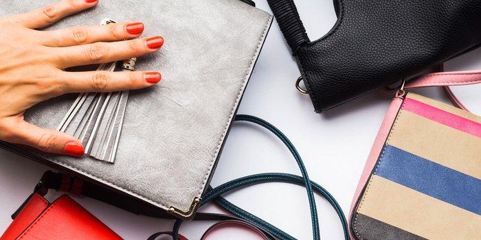 5b6db3a1040e0b Eine Hand mit rot lackierten Nägeln liegt auf einer silbernen Handtasche